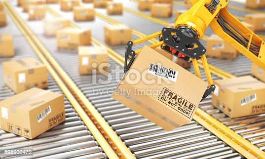 istock Factory manipulator. Automatic hand hold the cardboard box above conveyor. 898902472