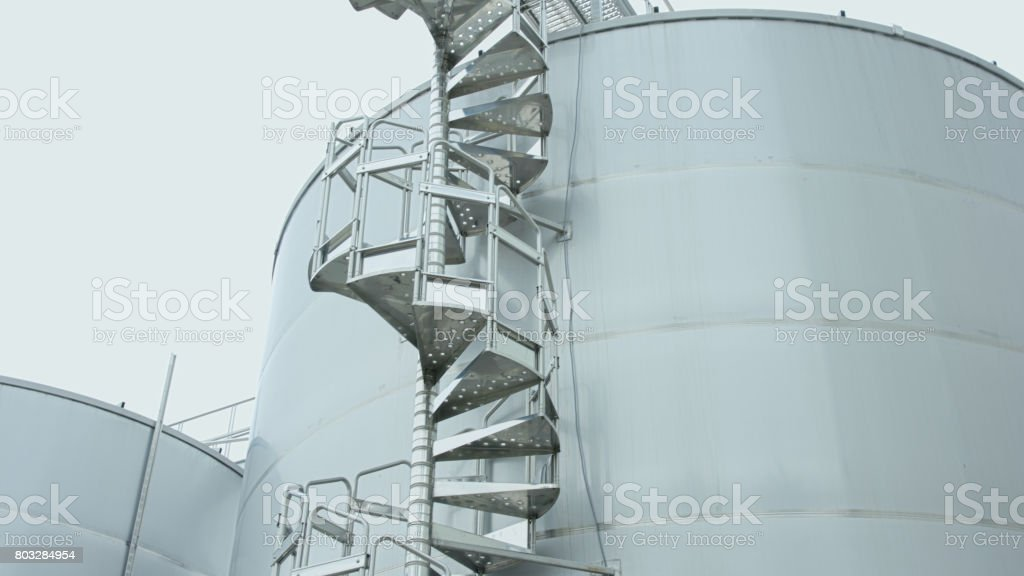 Factory. Metal staircase to storage tank stock photo