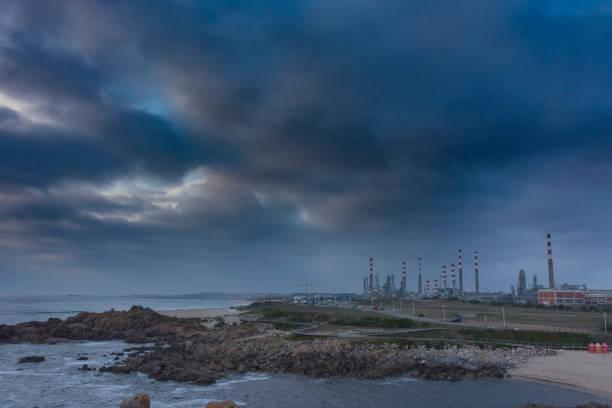 factory next to the coast - rain clouds porto portugal imagens e fotografias de stock