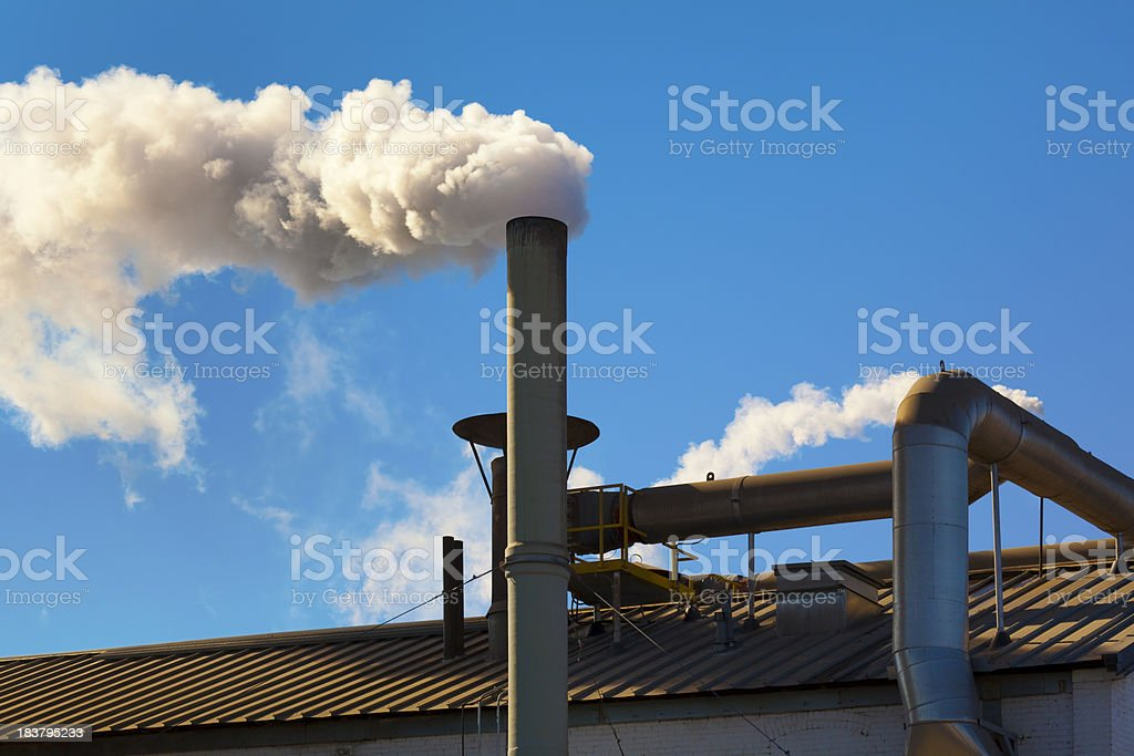 Factory Smokestack Billowing Dirty Pollutants Into Air, Blue Sky royalty-free stock photo