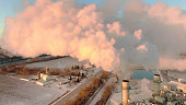 istock Factory smokestacks filling cold Winter air with warm emissions. 1203228971