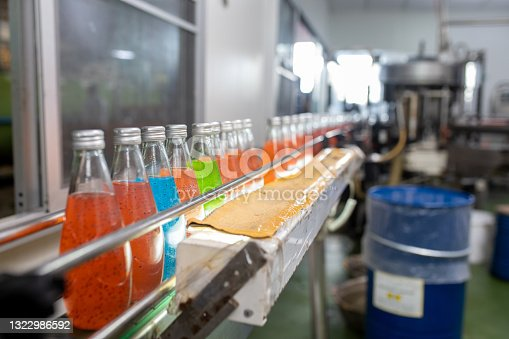istock factory spilling juice bottles into glass bottles on conveyor lines. Industrial work, automated production of food and drinks. Glass products. Bottles for drinks 1322986592