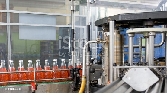 istock factory spilling juice bottles into glass bottles on conveyor lines. Industrial work, automated production of food and drinks. Glass products. Bottles for drinks 1322986623
