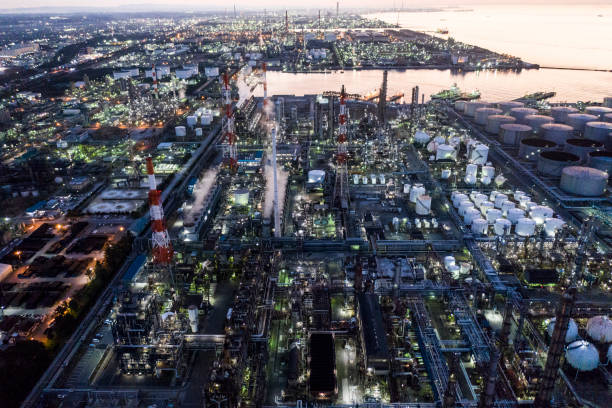 A factory that starts to light up at dusk and a beautiful sea stock photo