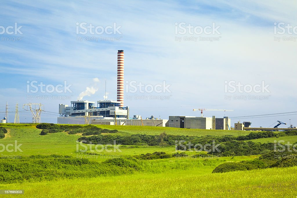 Factory with tall chimney in a green landscape royalty-free stock photo