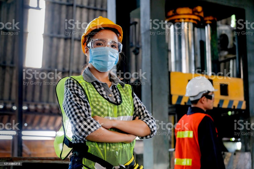 De werknemer van de fabrieksvrouw of de technicus met hygiënische maskertribune met vertrouwenactie met haar medewerker als achtergrond - Royalty-free Alleen volwassenen Stockfoto