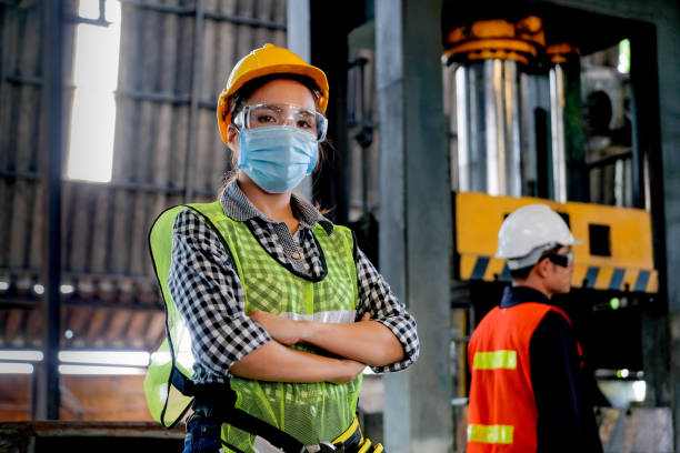 Factory woman worker or technician with hygienic mask stand with confident action with her co-worker  as background Factory woman worker or technician with hygienic mask stand with confident action with her co-worker  as background. covid mask stock pictures, royalty-free photos & images