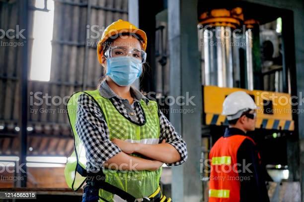 De Werknemer Van De Fabrieksvrouw Of De Technicus Met Hygiënische Maskertribune Met Vertrouwenactie Met Haar Medewerker Als Achtergrond Stockfoto en meer beelden van Alleen volwassenen