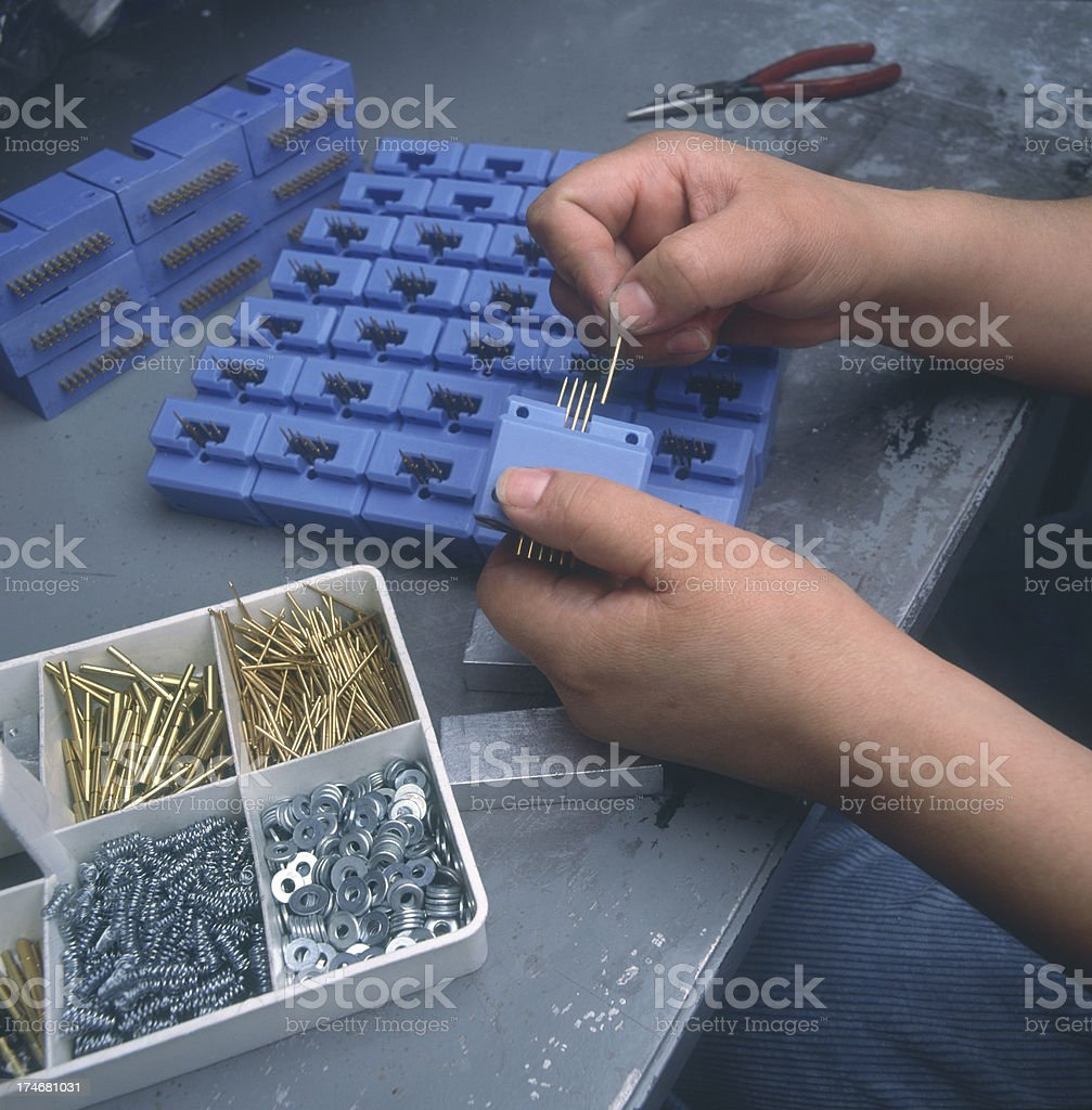 Factory worker assembles electrical connector stock photo