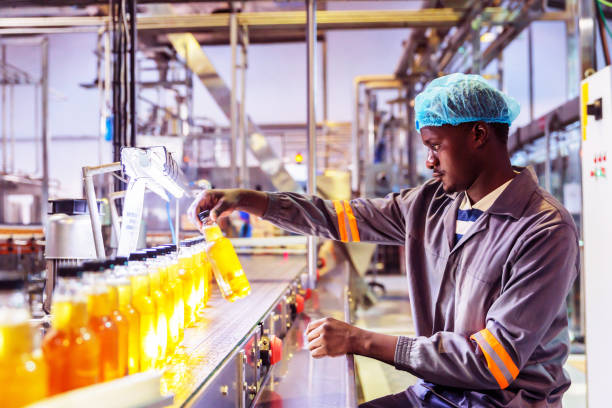 Factory Worker Checking Bottle on the Conveyor Belt stock photo