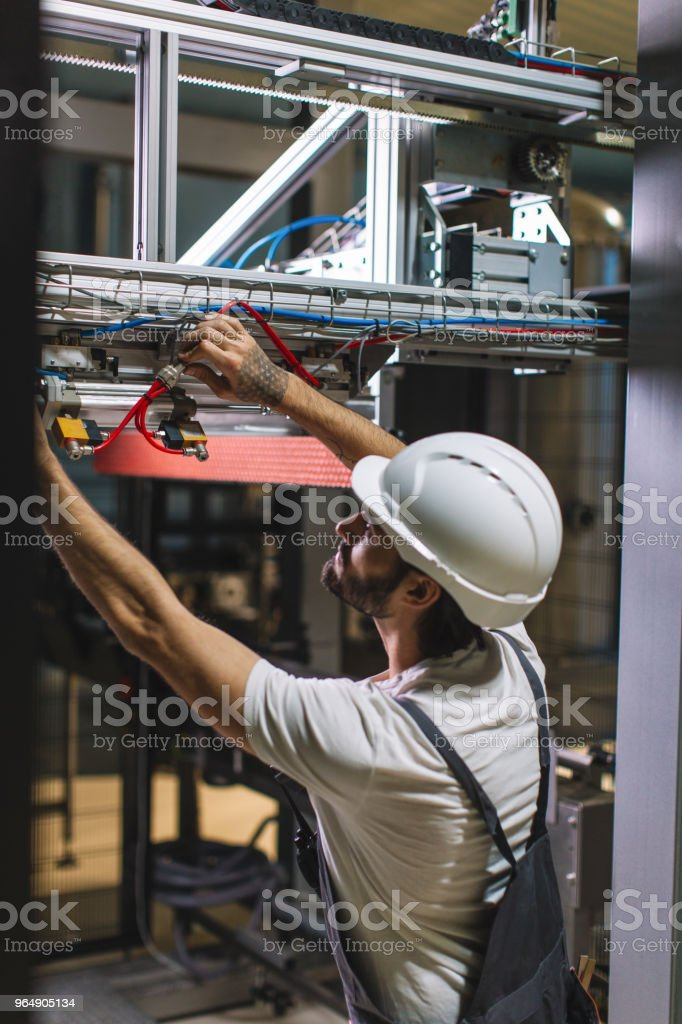 Factory worker controlling electrical installation royalty-free stock photo
