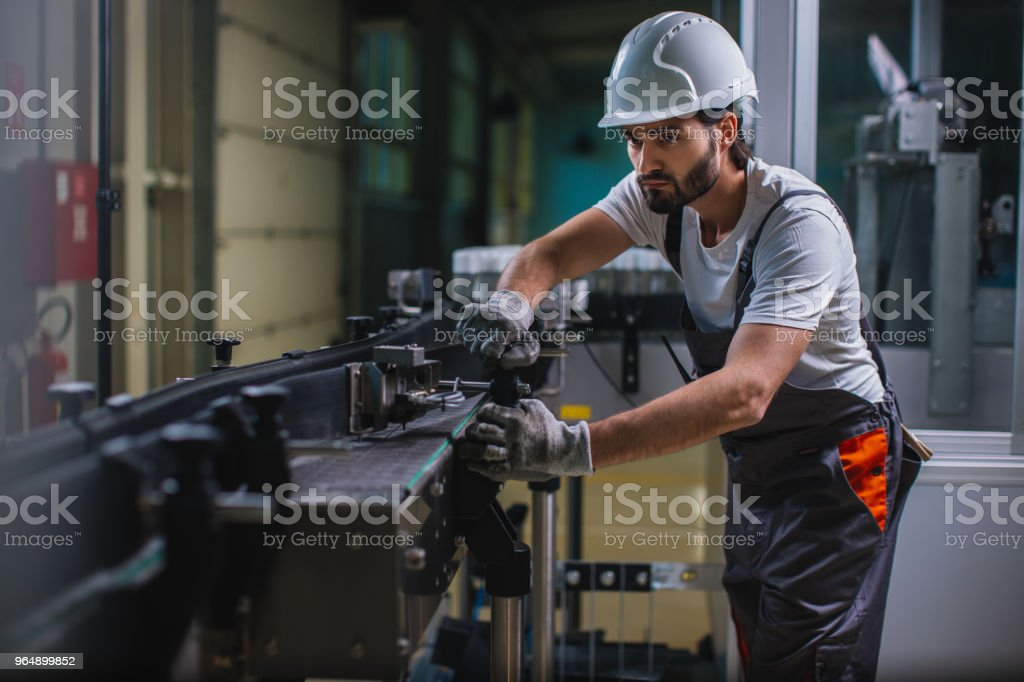 Factory worker controlling  machine at the manufacture royalty-free stock photo