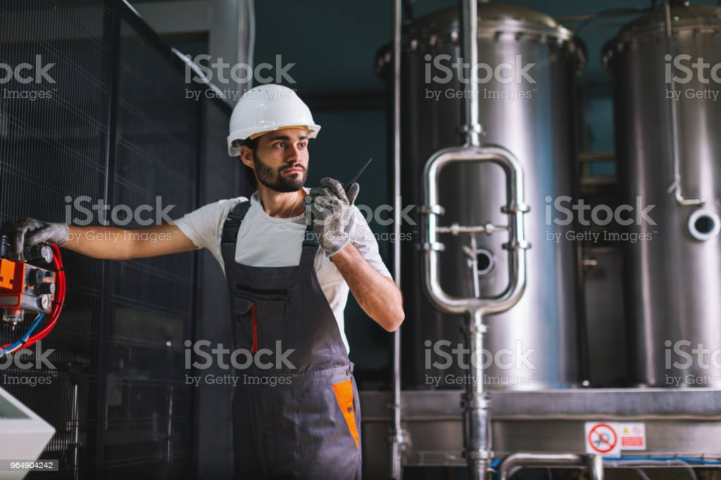Factory worker controlling production and talking and walkie-talkie with colleague stock photo
