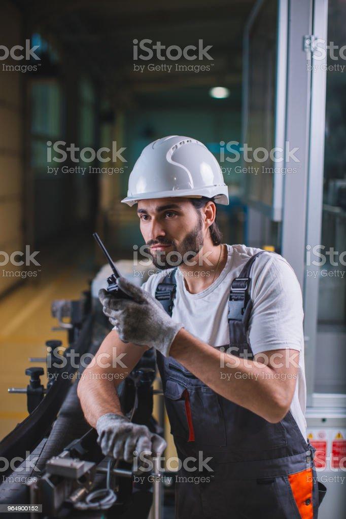 工廠工人控制生產和與同事交談對講機 - 免版稅一個人圖庫照片