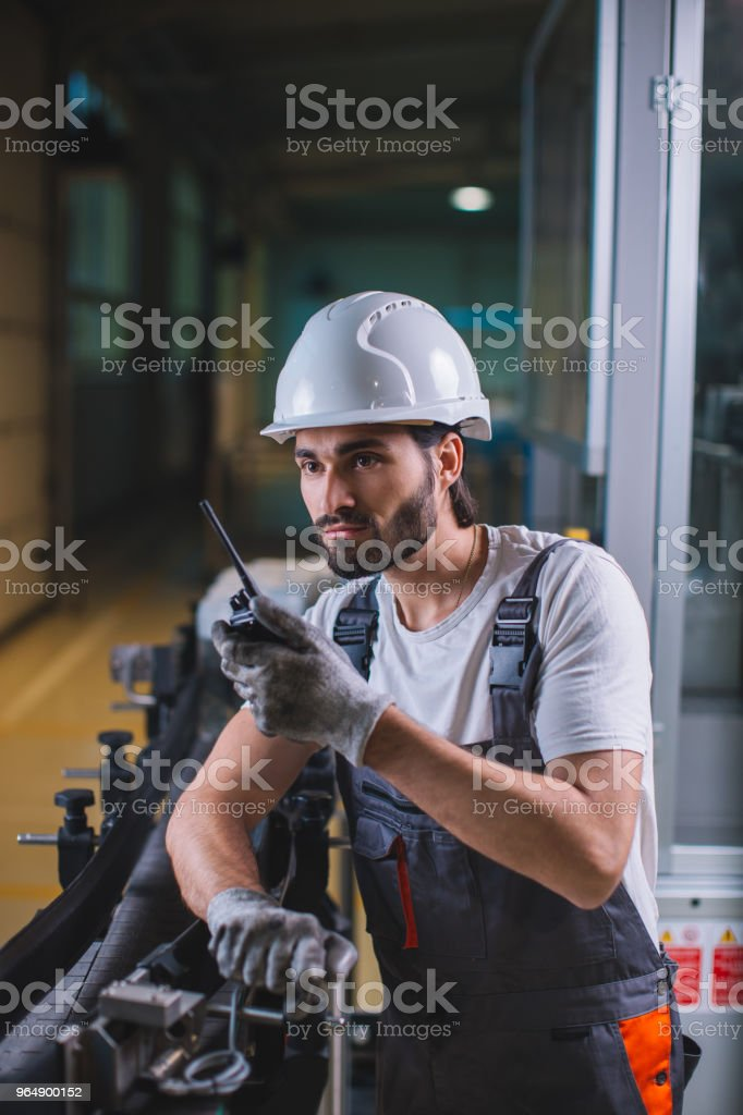 Factory worker controlling production and talking with colleague on walkie-talkie stock photo