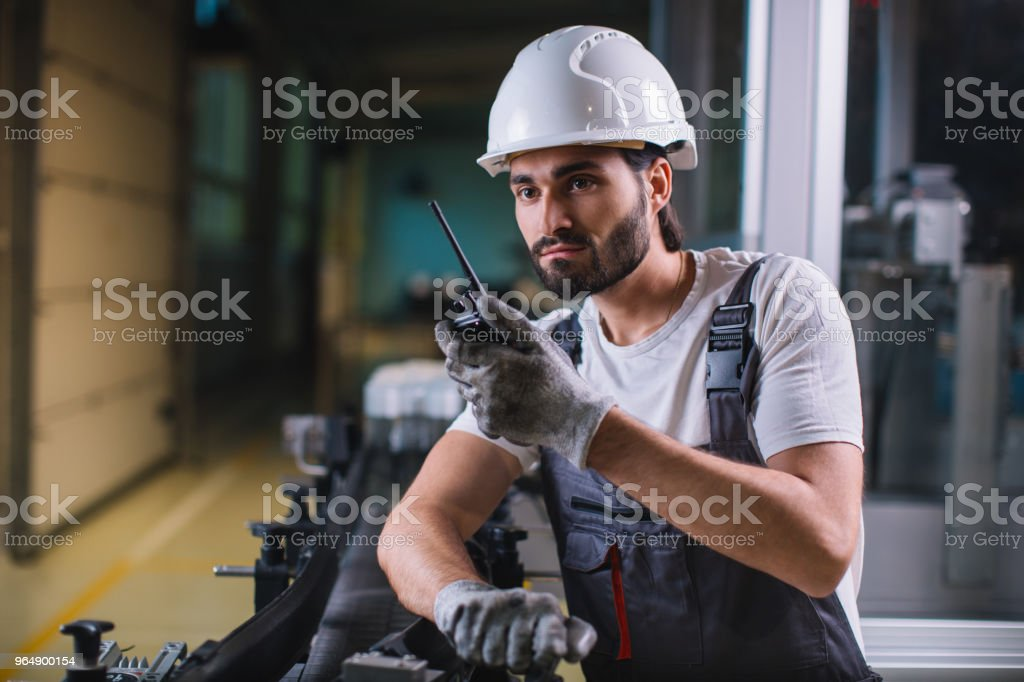 Factory worker controlling production and talking with colleague on walkie-talkie royalty-free stock photo