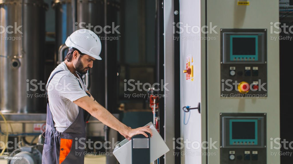 Factory worker controlling production on touch screen control panel royalty-free stock photo