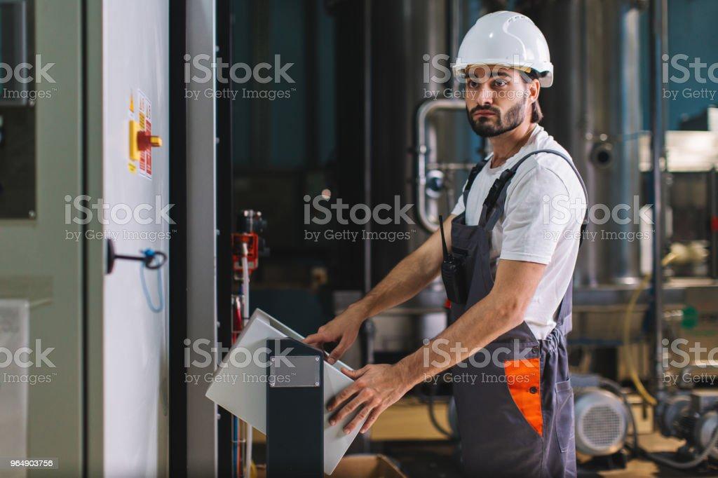觸控式螢幕控制台上的工廠工人控制生產 - 免版稅一個人圖庫照片
