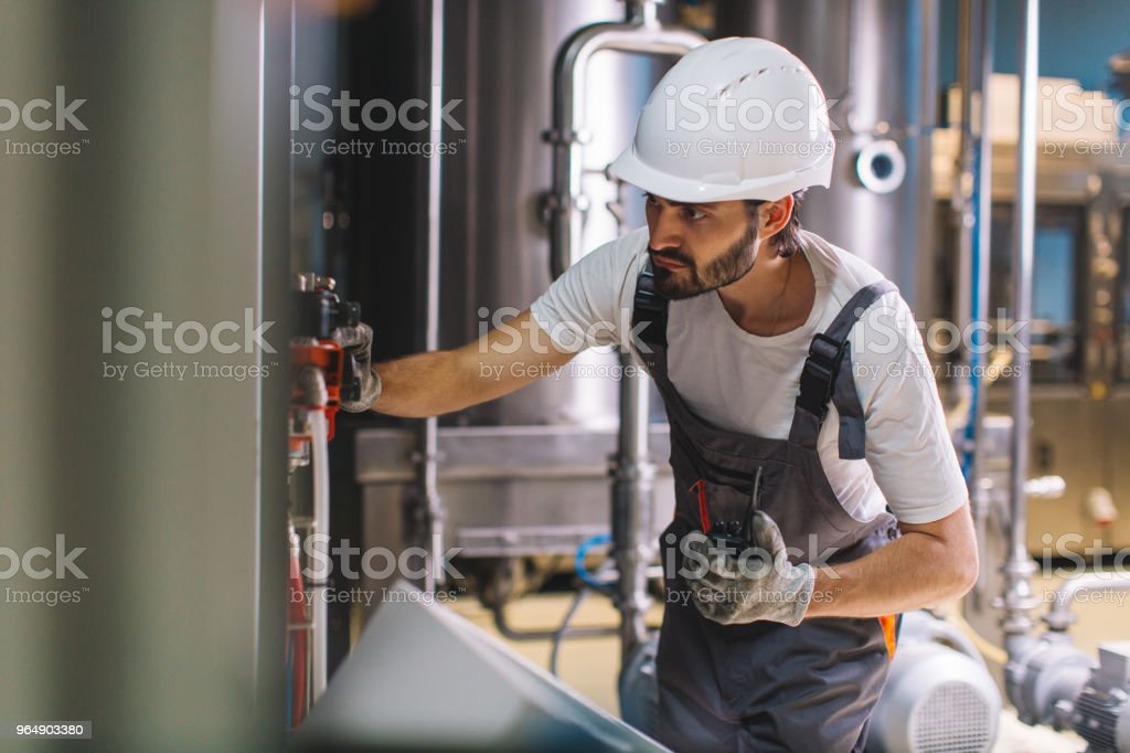 Factory worker controlling working instruments royalty-free stock photo