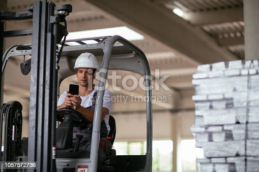 Factory worker driving the forklift. Shadow DOF. Developed from RAW; retouched with special care and attention; Small amount of grain added for best final impression. 16 bit Adobe RGB color profile.