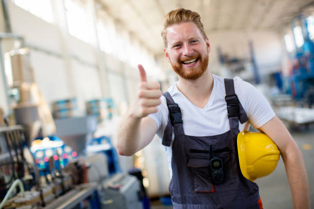 Factory worker holding thumbs up stock photo