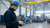 istock Factory worker in a hard hat is using a laptop computer with an engineering software. 838527654