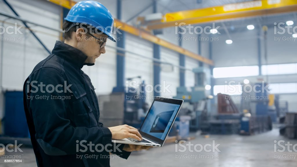 Factory worker in a hard hat is using a laptop computer with an engineering software. stock photo