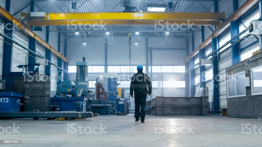 Factory worker in a hard hat is walking through industrial facilities. stock photo