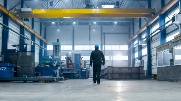factory worker in a hard hat is walking through industrial facilities. - factory imagens e fotografias de stock