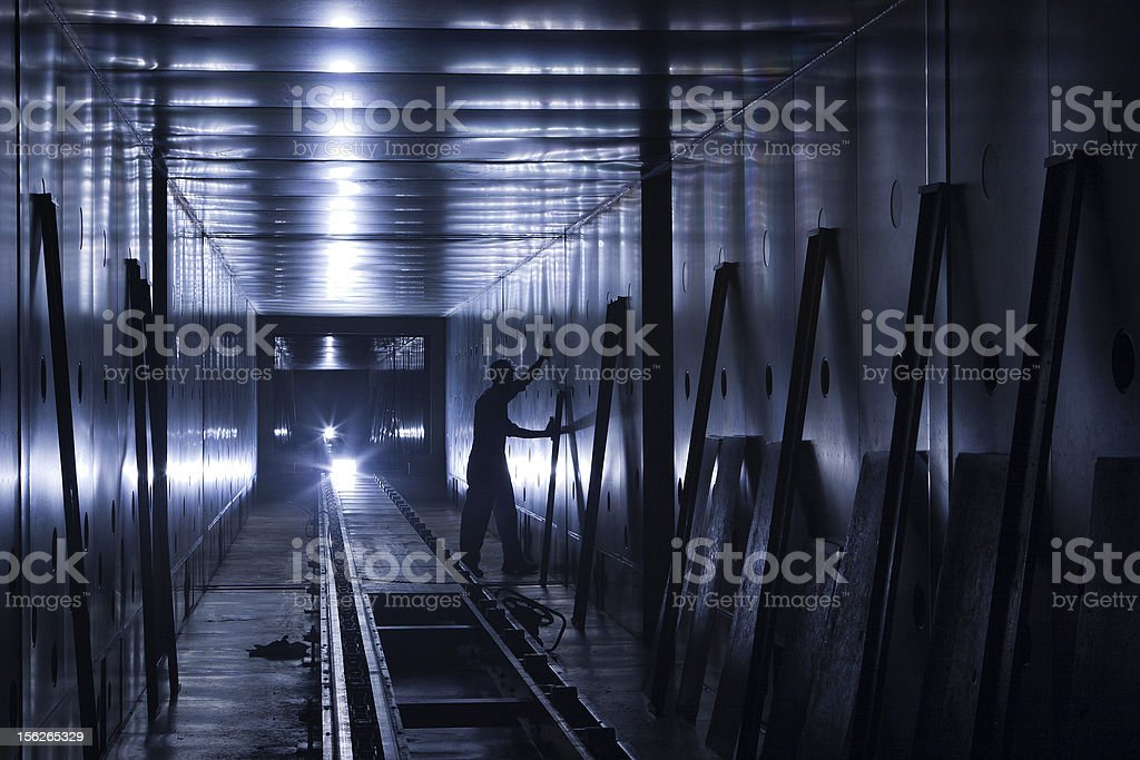 Factory worker in dimly lit tunnel stock photo