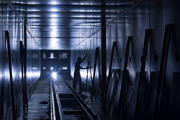 factory worker in dimly lit tunnel - dimly stock pictures, royalty-free photos & images