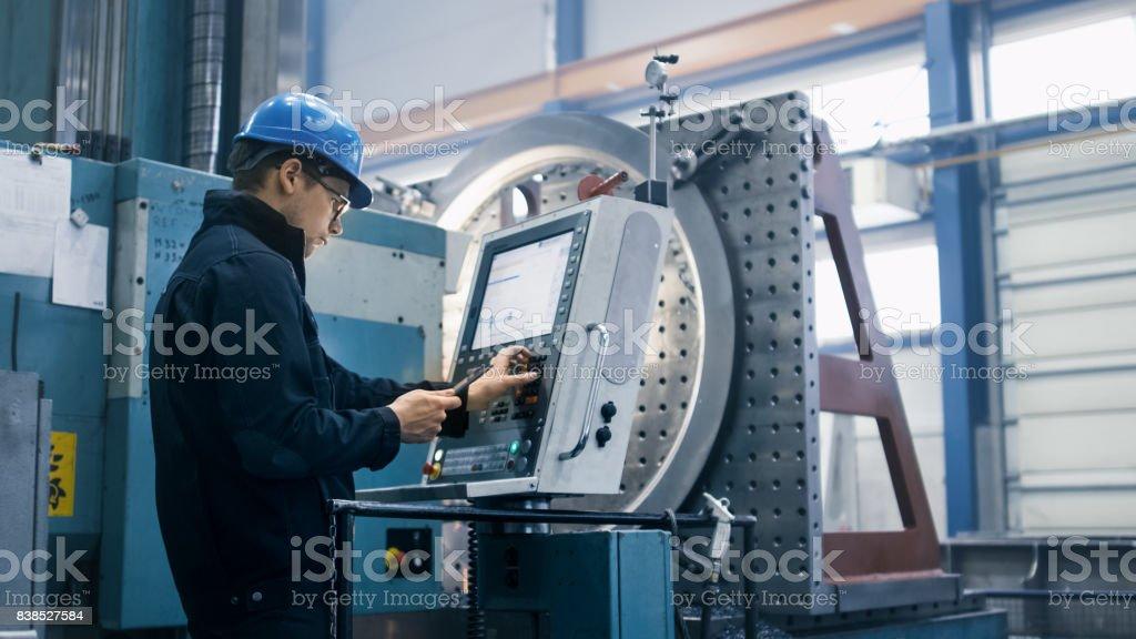 Ouvrier d'usine est de programmation une fraiseuse CNC avec une tablette PC. photo libre de droits