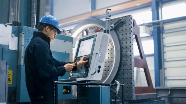 Ouvrier d'usine est de programmation une fraiseuse CNC avec une tablette PC. - Photo