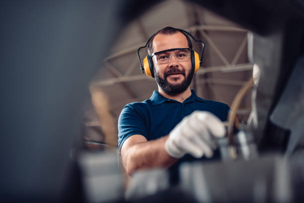 Factory worker operating band saw cutting machine Factory worker operating band saw cutting machine for steel bars in the industrial factory manufacturing stock pictures, royalty-free photos & images