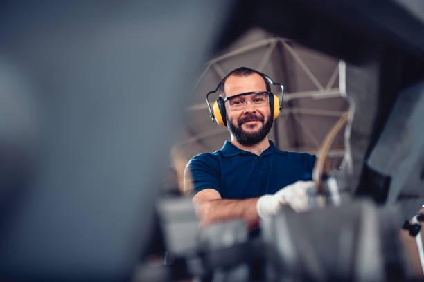 Factory worker operating band saw cutting machine stock photo