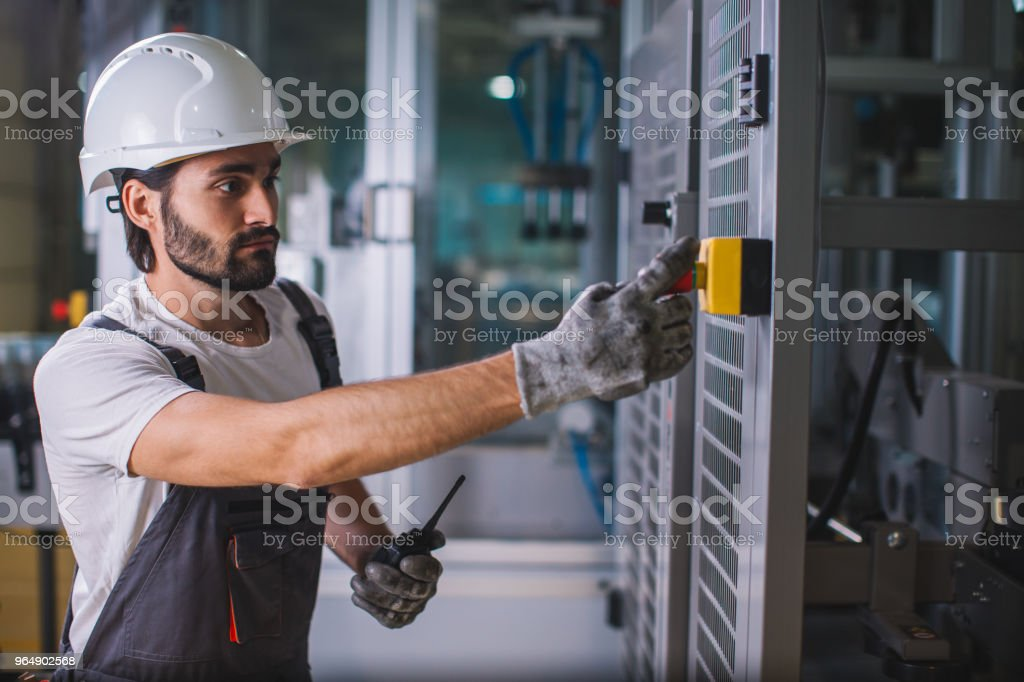 Factory worker starting production royalty-free stock photo
