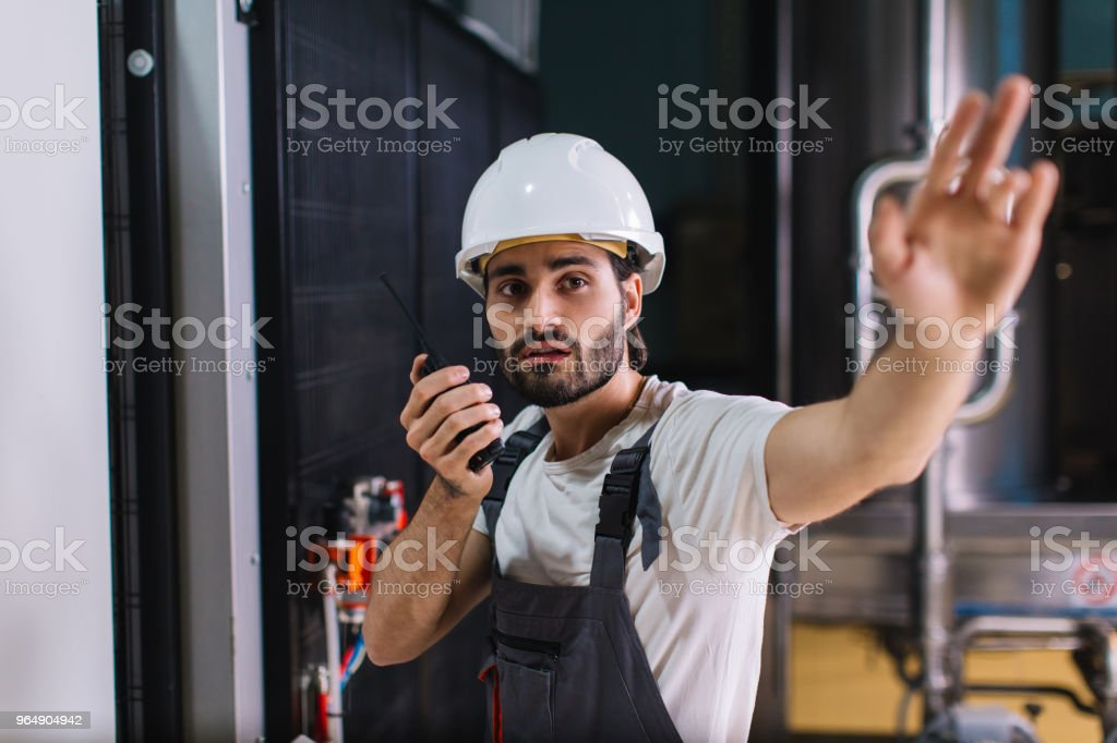 Factory worker talking with colleague on walkie-talkie royalty-free stock photo
