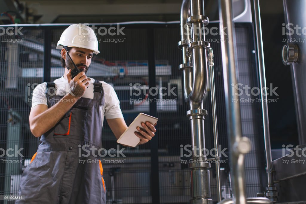 Factory worker talking with colleague on walkie-talkie stock photo
