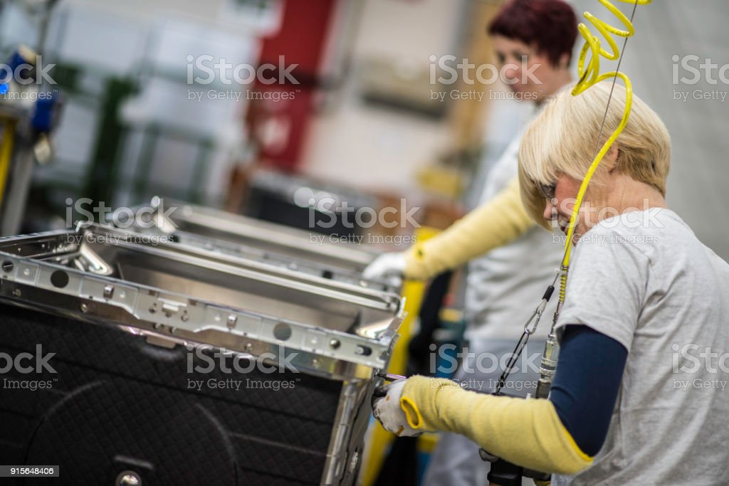 Factory worker tightening the screws on product stock photo