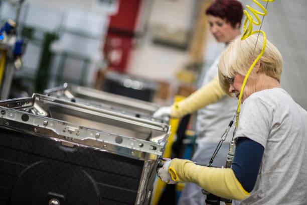 Ouvrier d'usine serrant les vis sur le produit - Photo