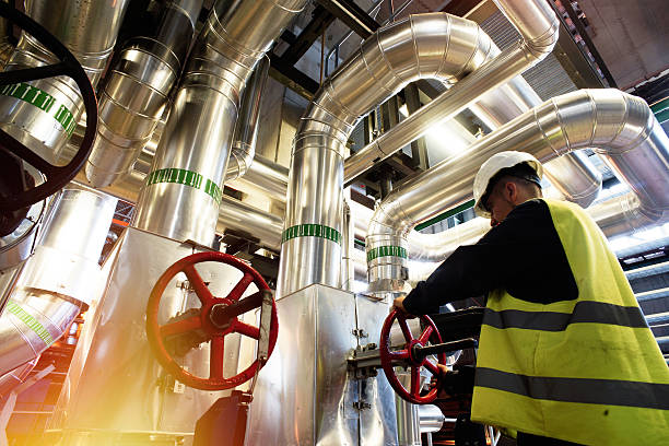 factory worker turning valve modern factory worker turning valve chemical plant stock pictures, royalty-free photos & images
