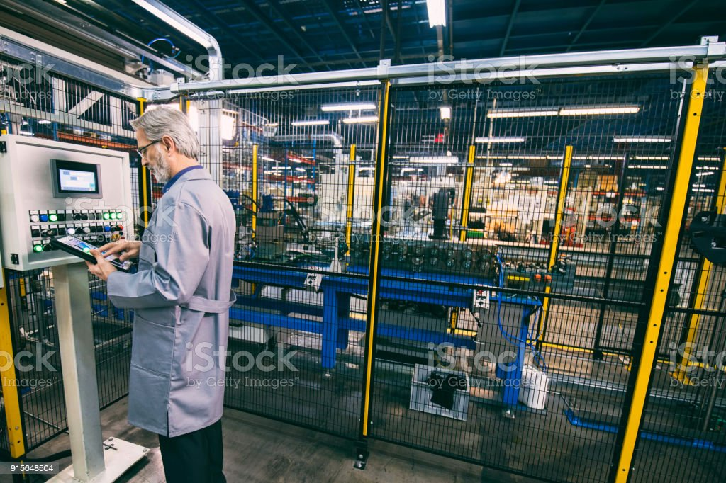 Factory worker updating control panel Male factory worker updating control panel using digital tablet in appliance manufacturing factory. 50-54 Years Stock Photo