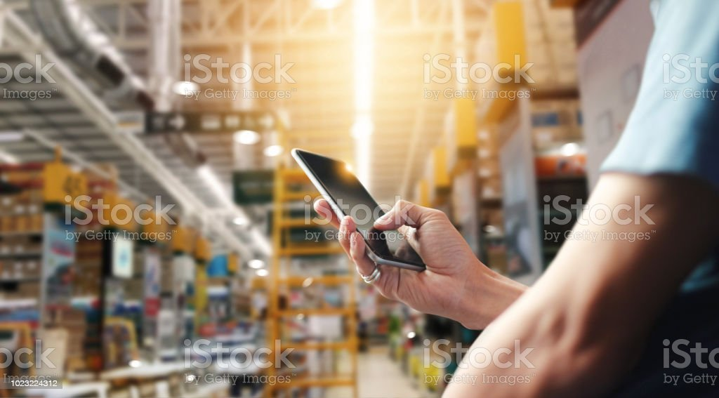 Factory worker using application on mobile smartphone to operate automation for modern trade. Checking order in large warehouse. Import and export the shipping cargo. - Zbiór zdjęć royalty-free (Bankowość)