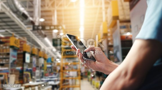 istock Factory worker using application on mobile smartphone to operate automation for modern trade. Checking order in large warehouse. Import and export the shipping cargo. 1023224312