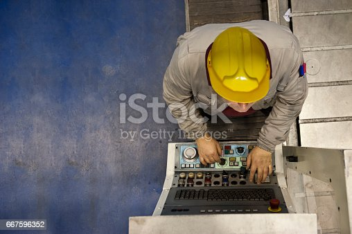 Factory worker using computer to operate automation, directly above