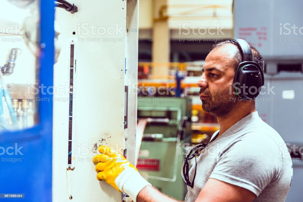 Factory Worker Using Computer to Operate Automation stock photo