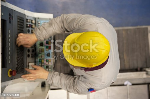 667596352istockphoto Factory worker using computer to operate machine 667778068