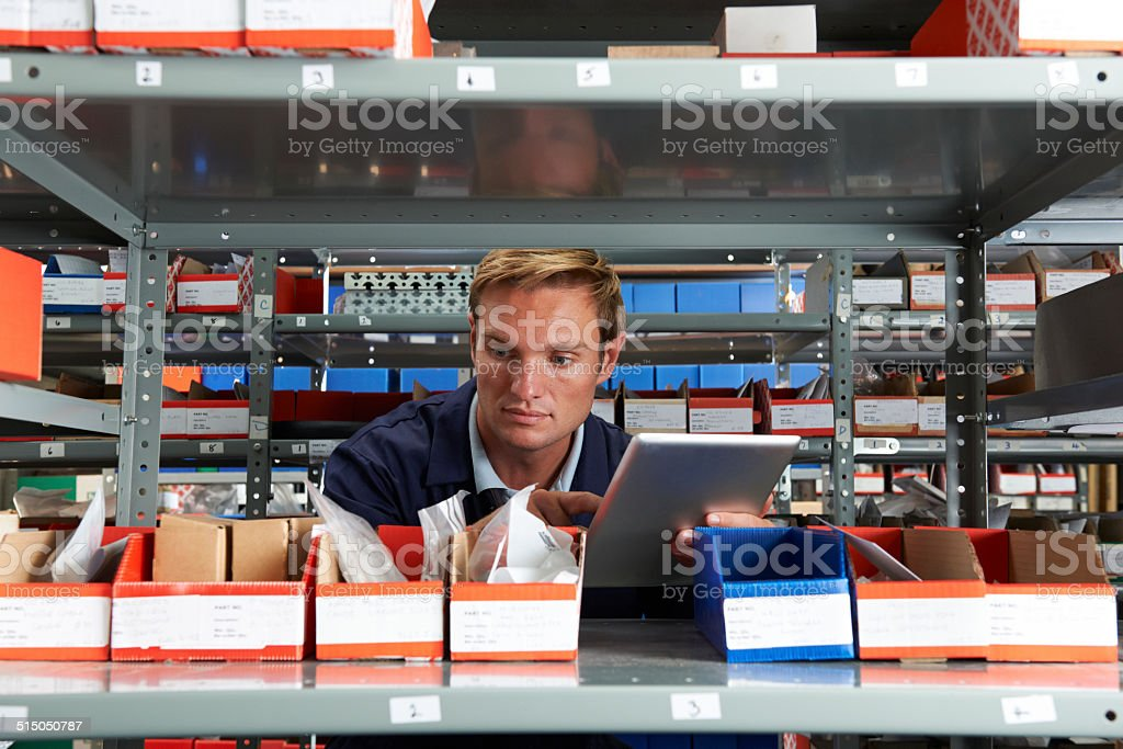 Factory Worker Using Digital Tablet In Store Room Factory Worker Using Digital Tablet In Store Room 30-39 Years Stock Photo