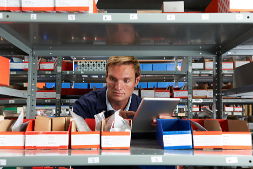 Factory Worker Using Digital Tablet In Store Room Stock Photo - Download Image Now