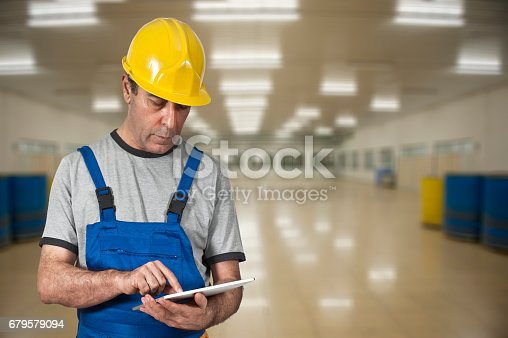 667596352istockphoto Factory worker using digital tablet 679579094